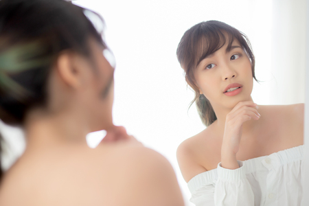 Beauty portrait young asian woman smiling look at mirror of checking skin care caucasian with wellness in the bedroom, beautiful girl happy touching face in reflection for health, lifestyle concept.