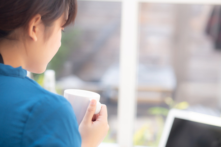 Beautiful young freelance asian woman smiling working and on laptop computer at desk coffee shop with professional, asia girl using notebook and drink coffee, business and lifestyle concept, back view.