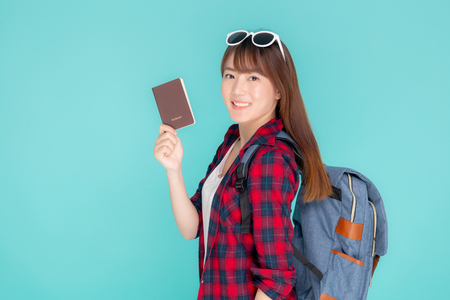 Beautiful portrait young asian woman wear sunglasses on head and backpack smile confident enjoy summer holiday isolated blue background, model girl fashion hipster holding passport, travel concept. Stock Photo