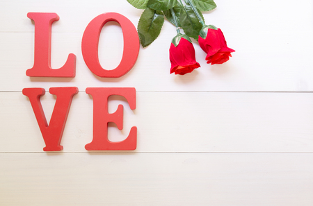 Word LOVE wooden text and red rose flower vintage on wood table vintage retro tone, 14 February of love day with romantic, valentine holiday concept, top view.
