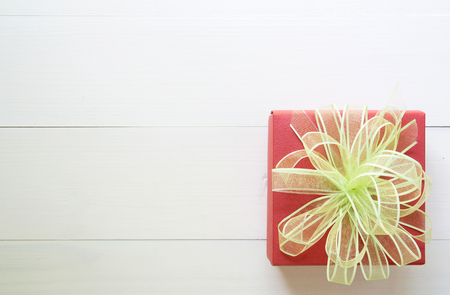 Holiday of gift box with bow ribbon on wooden white table, present of day on wood, top view, vintage retro tone, 14 February of love day with romantic copy space, valentine concept, top view.