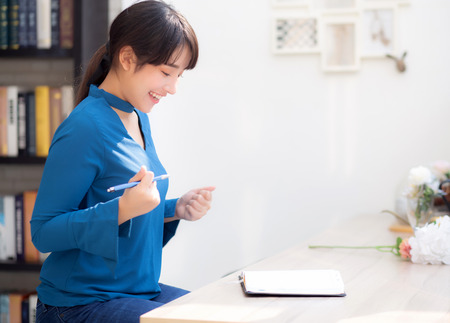Beautiful portrait young asian woman writer writing on notebook or diary with happy and excited, lifestyle asia girl planning working and success, education and business concept. Stock Photo
