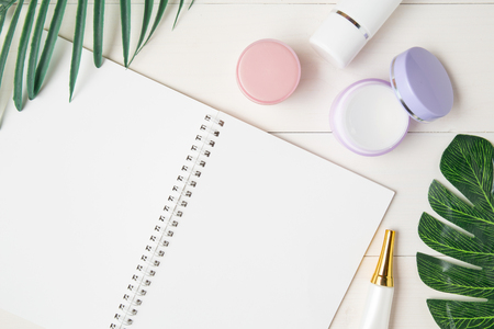 cosmetic and skin care product and notebook and leaves on table, beauty with treatment cream and moisturizing and notepad copy space on wooden desk, health and wellness concept, top view.