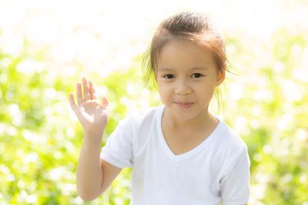 Porträtgesicht des süßen asiatischen kleinen Mädchens und Kinderglücks und -spaßes im Park im Sommer, Lächeln und glücklich von Asien-Kind und Entspannung im Garten, Lifestyle-Kindheitskonzept. Standard-Bild