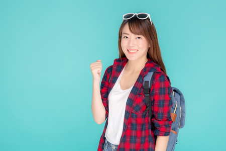 Beautiful portrait young asian woman wear sunglasses on head smile confident and excited summer holiday isolated blue background, model girl fashion having backpack, travel concept.