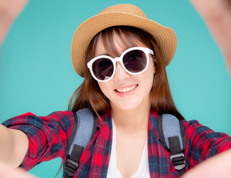 Beautiful young asian woman taking selfie with camera for relax in vacation isolated on blue background, asia girl wear clothes casual travel summer fashion excited, tourist and journey concept.