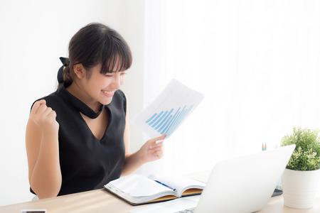 Beautiful young asian woman working laptop computer at office, businesswoman looking graph diagram analysis statistic data with excited and success, girl using notebook, business concept. Reklamní fotografie