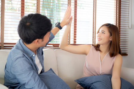 Beautiful young asian couple man and woman gesture hi five together with relax after work success on sofa, family celebration enjoy and excited with happy on couch, lifestyle concept.