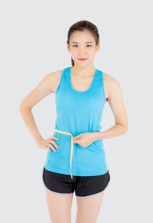 Beautiful slim young asian woman measuring tape thin waist wear uniform fitness isolated white background, asia girl loss weight for diet with exercise and workout wellbeing and healthy care body.