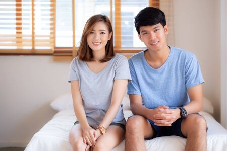 Beautiful portrait young asian couple relax and satisfied together in bedroom at home, family sitting on bed confident with cheerful and happy with relationship, man and woman dating.