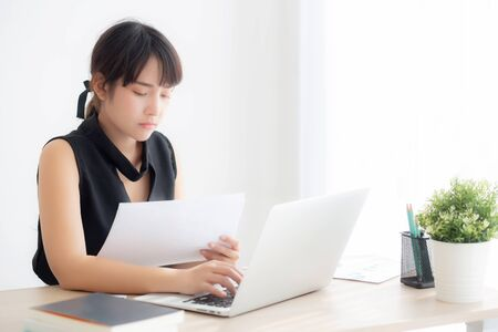 Beautiful young asian woman working and typing with laptop computer at office Stockfoto