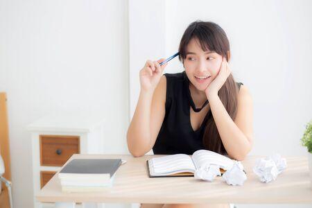 Mooie aziatische vrouwenschrijver die lacht en een idee schrijft op een notebookdagboek met planning die aan een bureau werkt