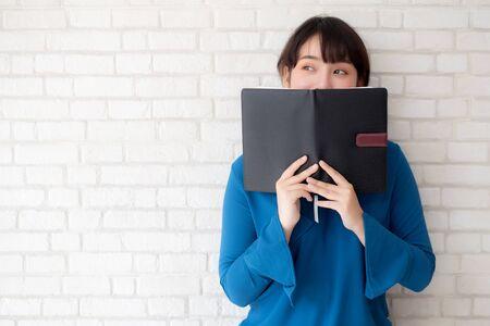 Hermoso retrato joven mujer asiática feliz escondiéndose detrás de cubrir el libro con cemento o ladrillo de fondo concreto, niña de pie leyendo un cuaderno abierto para el aprendizaje, la educación y el concepto de conocimiento.