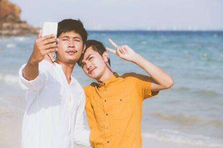 Pareja joven retrato gay sonriendo tomando una foto selfie junto con teléfono móvil inteligente en la playa, amante LGBT en las vacaciones en el mar, dos hombres que van a viajar, concepto de vacaciones.