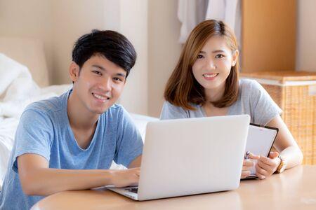 La bella giovane coppia asiatica calcola la finanza delle spese con il computer portatile e pianifica insieme, la donna che scrive il taccuino o nota il bilancio familiare, lo stile di vita familiare e il concetto di affari.