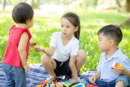 Kleine jongen en meisje spelen voor idee en inspiratie met speelgoedblok, kind leren met bouwblok voor onderwijs, kinderactiviteit en spel in het park met gelukkig in de zomer.
