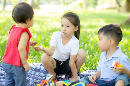 Little boy and girl is playing for idea and inspiration with toy block, kid learning with construction block for education, child activity and game in the park with happy in the summer.