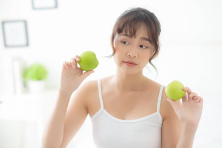 Beautiful portrait young asian woman holding and eating green apple fruit in the bedroom at home, lifestyle of nutrition girl healthy and care weight loss, health and wellness concept.