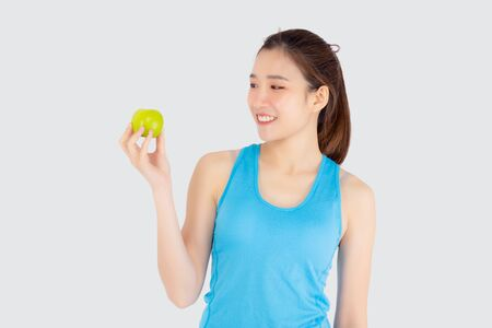 Beautiful portrait young asian woman in sport clothing with satisfied and holding green apple isolated on white background, girl asia have shape and wellness, exercise for fit with health concept.
