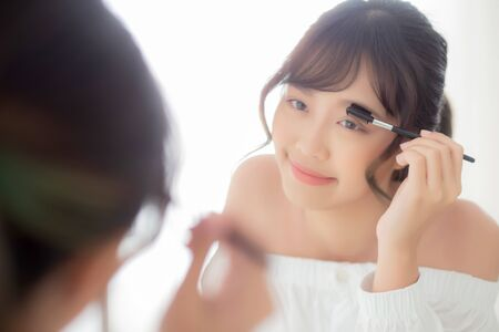 Beautiful young asian woman applying makeup eyebrows brush, beauty asia girl using cosmetic for make up style looking mirror at home, fashion female tweezing with natural, lifestyle concept. Imagens