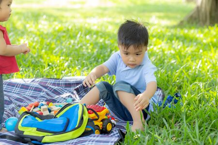 Little boy is playing for idea and inspiration with toy block in the grass field, kid learning with construction block for education, child activity and game in the park with happy in the summer. Stock Photo