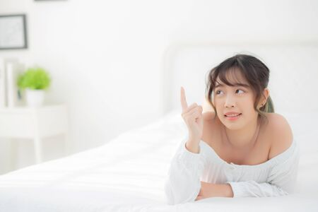 Portrait beautiful young asian woman smile wake up healthy and wellness at morning, beauty asia girl lying and pointing something skin care and makeup cosmetic with happy, lifestyle and relax concept.