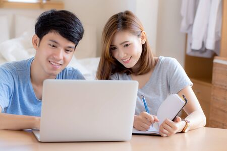 Beautiful young asian couple calculate expenses finance with laptop and planning together, woman writing notebook or note budget household, lifestyle family and business concept.
