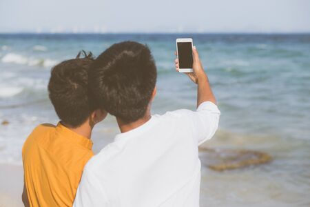Vista posterior retrato joven pareja sonriendo tomando una foto selfie junto con teléfono móvil inteligente en la playa, amante LGBT en las vacaciones en el mar, dos hombres van a viajar, concepto de vacaciones.