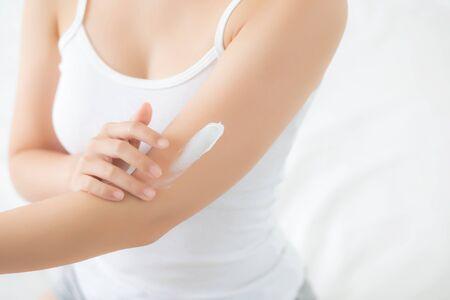 Gros plan sur une belle jeune femme asiatique souriante appliquant une lotion crème solaire sur les soins de la peau dans la chambre à coucher, le maquillage et les cosmétiques de la beauté asiatique pour un concept lisse et soyeux, de bien-être et de santé.