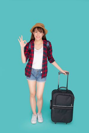 Beautiful young asian woman pulling suitcase isolated on blue background, asia girl cheerful holding luggage walking and gesture ok in vacation with excited, journey and travel concept. 写真素材
