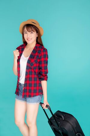 Beautiful young asian woman pulling suitcase isolated on blue background, asia girl having expression cheerful and success holding luggage walking in vacation with excited, journey and travel concept.