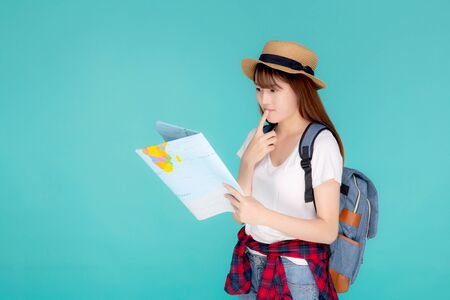 Beautiful portrait young asian woman travel holding and looking a paper map isolated on blue Stockfoto