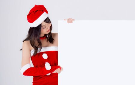 Beautiful young asian Santa woman holding blank board for xmas isolated on white Stockfoto