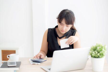 Belle jeune femme asiatique calculant les dépenses du ménage et écrivant le cahier sur le bureau