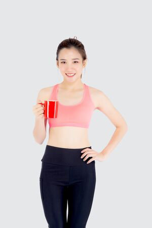 Hermosa joven asiática en el deporte después del entrenamiento bebiendo agua de vidrio para sed aislado en blanco