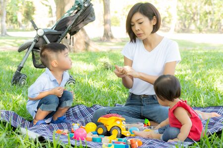 Beautiful young asian mom and daughter playing toy blocks for learning development happy and fun at park in summer Stockfoto