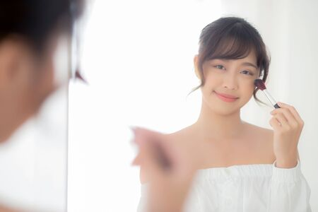Beauty portrait young asian woman smiling with face looking mirror applying makeup with brush cheek in the bedroom