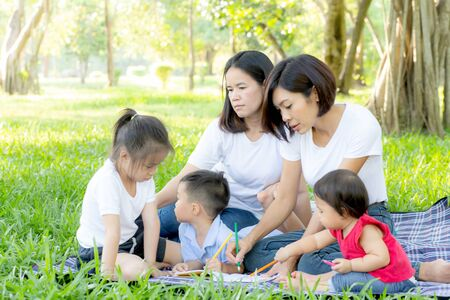 Beautiful young asian parent family portrait picnic in the park