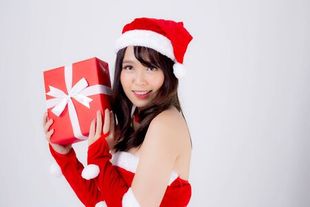 Beautiful portrait young asian woman happy holding red gift box with excited in xmas holiday isolated on white