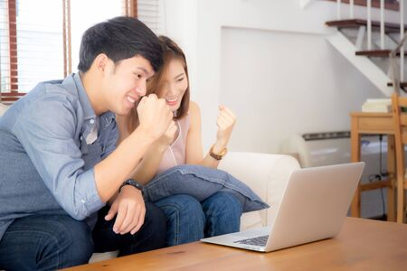 Beautiful portrait asian young couple working laptop with smile and happy sitting on couch at living room