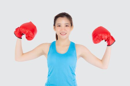 Beautiful portrait young asian woman wearing red boxing gloves flexing with strength and strength isolated on white
