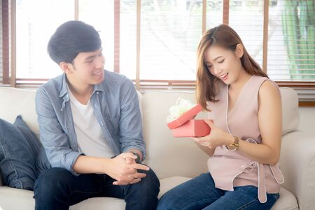 Young asian couple celebrate birthday together, asia man giving gift box present to woman for surprise at living room Stockfoto
