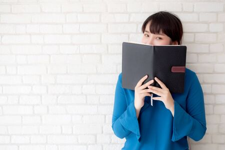 beautiful portrait young asian woman happy hiding behind covering the book with cement or brick concrete background, girl standing open notebook reading for learning, education and knowledge concept.