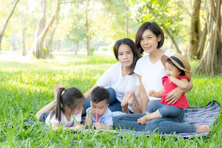 Beautiful young asian parent family portrait picnic in the park, kid or children and mother love happy and cheerful together in summer at garden, lifestyle concept.