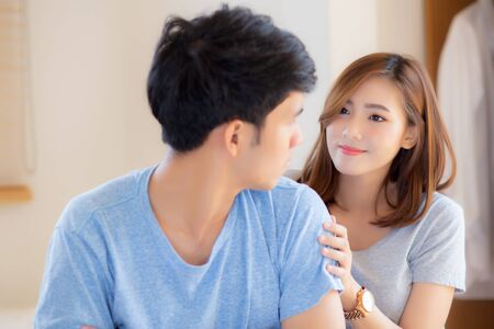 Young asian couple a problem and woman ask forgive and sorry with man feeling angry at bedroom, asia wife excuse convince husband with relationship, family and lifestyle concept.