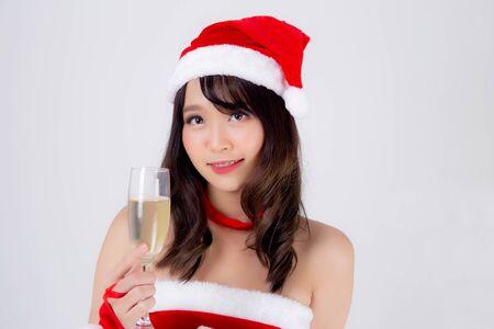 Junge asiatische Frau des schönen Porträts in Sankt, die Glas Champagner mit der Partei hält, die im Weihnachtsfeiertag lokalisiert auf weißem Hintergrund, Asien-Mädchengetränkgetränk, Weihnachten und Neujahrskonzept feiert. Standard-Bild
