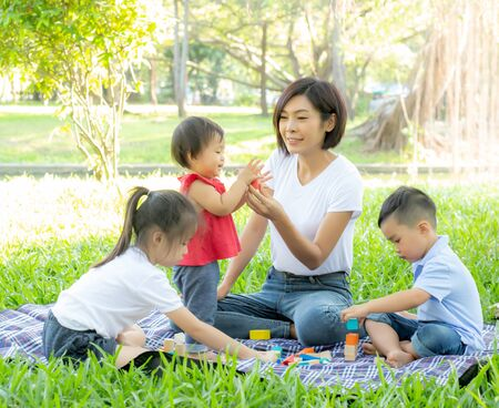 Beautiful young asian mom and daughter playing toy blocks for learning development happy and fun at park in summer, mother and kid cheerful activity together at garden in holiday, family concept.