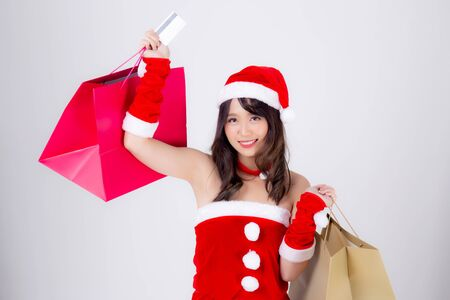 Beautiful portrait young asian woman smiling holding credit card and shopping paper bag with excited isolated on white background, beauty asia girl buying and payment in Christmas or new year holiday.