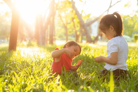 Beautiful young asian kid sitting playing in summer in the park with enjoy and cheerful on green grass, children activity with relax and happiness together on meadow, family and holiday concept. 스톡 콘텐츠