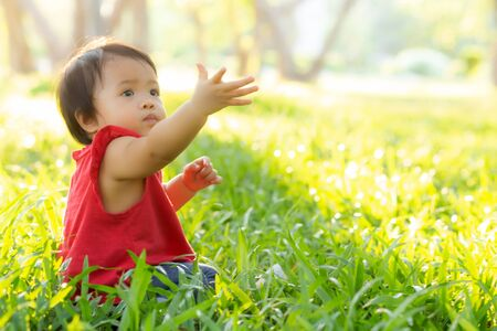 Portrait face of cute asian little girl and child happiness and fun in the park in the summer, smile and happy from asia kid and relax in the garden, lifestyle childhood concept.